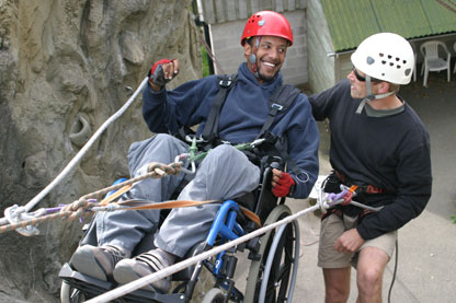 a guy in a wheelchair is laughing with his instructor. They are halfway up (or down!) a climbing wall.