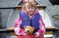 A young girl sits in a canoe with her teddy and life jacket, ready to depart.