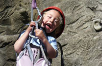 Happy hoisted - a young girl is happy, and in a hoist with a rock-face behind her.