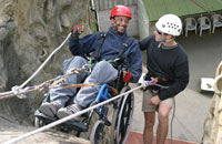 A man in a wheelchair is smiling with his instructor as he is abseiling down a quite steep slope!