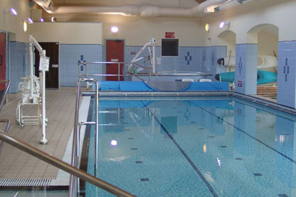 The swimming pool at exmoor. There are various devices around the side of the pool for assisting people. Canoes are visible also.