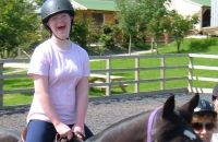 A girl learning to ride at the riding school. She is very happy on her horse.