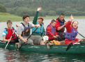 children and instructors on a canoe in a lake waving