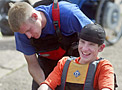 A volunteer helps a disabled boy into a canoe